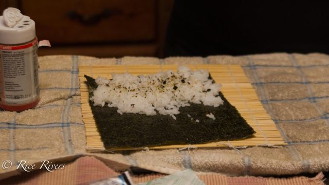 Take a bamboo sushi rolling sheet and place a piece of nori on it shiny side down. (Nori is the seaweed that sushi is rolled in)! Take sushi rice (we used Botan Rice) and cover about 1/3 of the nori closest to you, patting the rice down as you go. (Addition of seasonings as pictured here is optional).