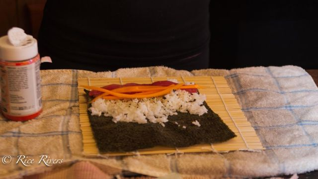 Add the sushi fillings that you would like making sure that they extend all the way to each side of the nori.