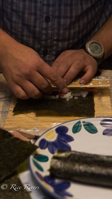 Begin to roll the bamboo mat away from you, using your other hand to hold the ingredients in.
